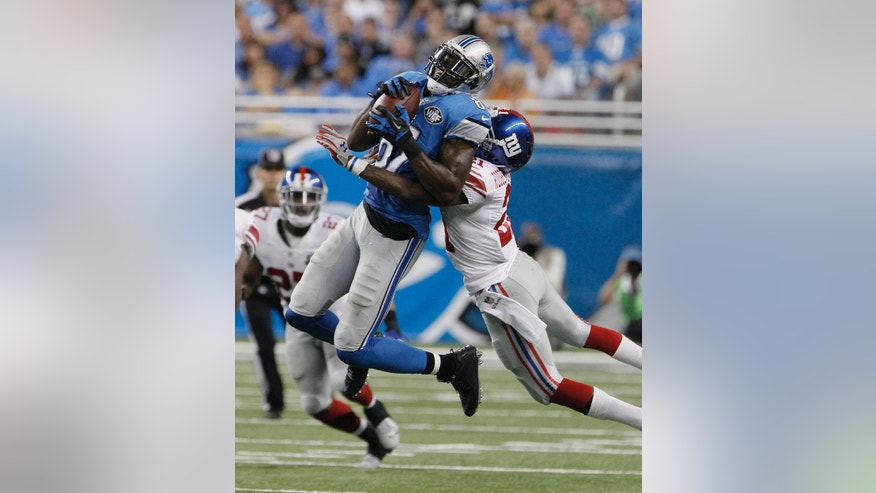 Detroit Lions wide receiver Calvin Johnson is stopped by New York Giants cornerback Dominique Rodgers-Cromartie (21) during the fourth quarter of an NFL football game against the in Detroit, Monday, Sept. 8, 2014. (AP Photo/Duane Burleson)