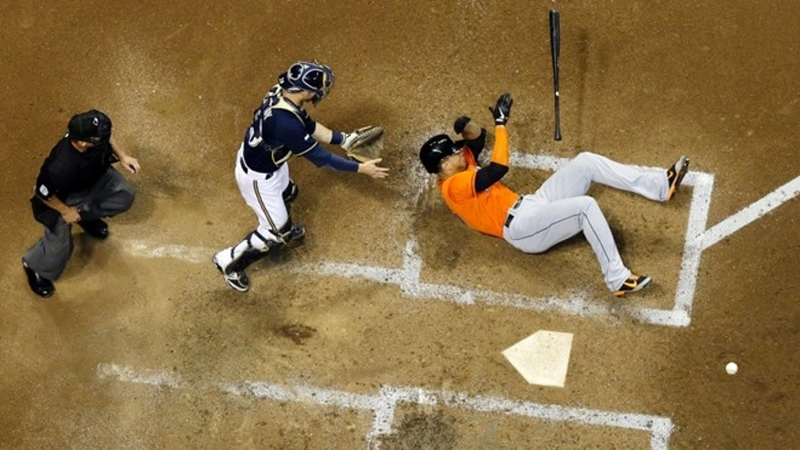 Miami Marlins' Giancarlo Stanton falls down after being hit in the face with a pitch during the fifth inning of a baseball game against the Milwaukee Brewers Thursday, Sept. 11, 2014, in Milwaukee. Stanton was taken off the field on a stretcher. (AP Photo/Morry Gash)