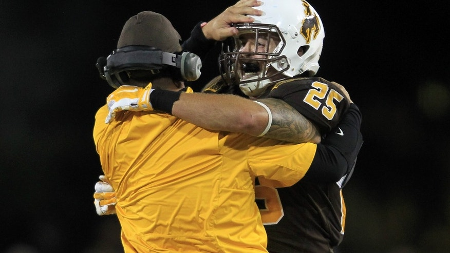 University of Wyoming tight end J.D. Krill celebrates with a coach after catching the winning touchdown with under a minute left in the game to help the Cowboys defeated Air Force Academy 17-13 on Saturday, Sept. 6, 2014 at War Memorial Stadium in Laramie, Wyo. (AP Photo/The Wyoming Tribune Eagle, Blaine McCartney)