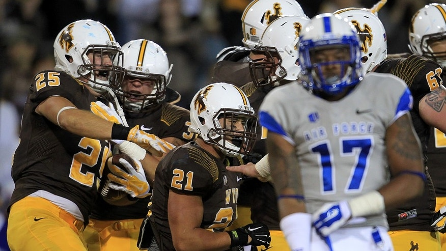 University of Wyoming tight end J.D. Krill (25) celebrates his teammates after catching the winning touchdown with under a minute left in the game to help the Cowboys defeated Air Force Academy 17-13 on Saturday, Sept. 6, 2014 at War Memorial Stadium in Laramie, Wyo. (AP Photo/The Wyoming Tribune Eagle, Blaine McCartney)