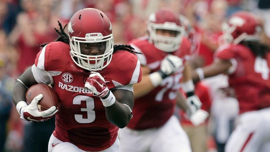 In this photo taken Sept. 6, 2014, Arkansas running back Alex Collins (3) carries in the first quarter of an NCAA college football game against Nicholls in Fayetteville, Ark. The Razorbacks, led by running backs Collins and Jonathan Williams hope to carry the momentum of Arkansas' 73-7 victory ahead to next week at Texas Tech. (AP Photo/Danny Johnston)