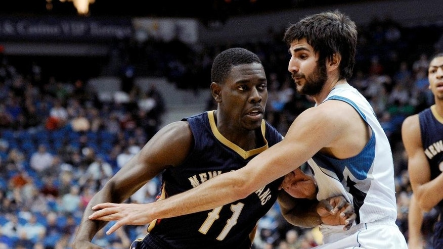 FILE - In this Jan. 1, 2014, file photo, Minnesota Timberwolves guard Ricky Rubio, right, defends New Orleans Pelicans guard Jrue Holiday (11) during an NBA basketball game in Minneapolis. Holiday missed more than half of last season with a stress fracture in his right tibia, which was surgically repaired on late February. Holiday recently started participating in five-on-five scrimmages and expected to participate fully in training camp, which begins Sept. 30. (AP Photo/Hannah Foslien, File)