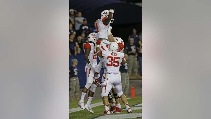 Houston wide receiver Daniel Spencer (4) is lifted to the air by teammates after scoring in the second quarter of an NCAA college football game against BYU,  Thursday, Sept. 11, 2014, in Provo, Utah.(AP Photo/Rick Bowmer)