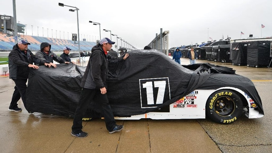 Timothy Peters' crews push his truck to the garage after rain forced the cancellation of qualifying for the NASCAR Camping World Truck Series auto race at Chicagoland Speedway in Joliet, Ill., Friday, Sept. 12, 2014. (AP Photo/Paul J. Bergstrom)