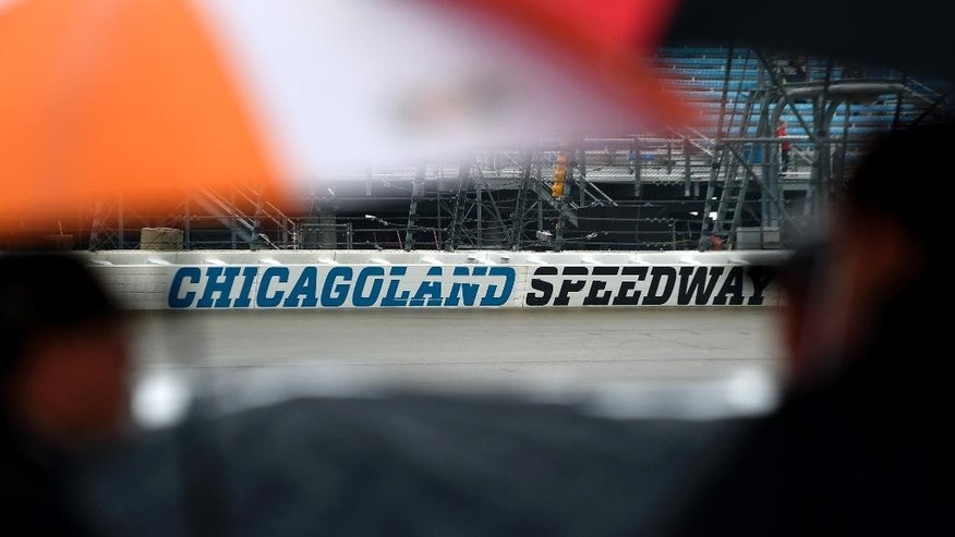 Pit crews wait under umbrellas during a rain delay in qualifying for the NASCAR Camping World Truck Series auto race at Chicagoland Speedway in Joliet, Ill., Friday, Sept. 12, 2014. (AP Photo/Paul J. Bergstrom)