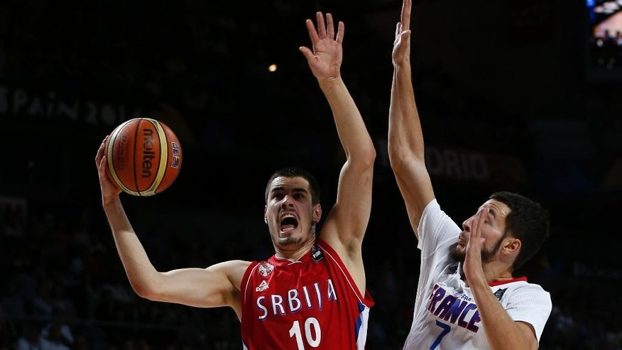Serbia's Nikola Kalinic challenges for the ball with France's Joffrey Lauvergne during a basketball World Cup semifinal match between France and Serbia at the Palacio de los Deportes stadium in Madrid, Spain, Friday, Sept. 12, 2014. (AP Photo/Daniel Ochoa de Olza)