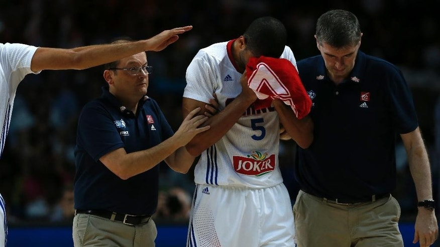 France's Nicolas Batum leaves the pitch after being injured on a drive to the basket during a basketball World Cup semifinal match between France and Serbia at the Palacio de los Deportes stadium in Madrid, Spain, Friday, Sept. 12, 2014. (AP Photo/Daniel Ochoa de Olza)