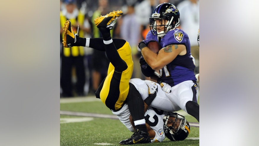 Baltimore Ravens tight end Owen Daniels (81) hangs on to the ball as he is tackled by Pittsburgh Steelers free safety Mike Mitchell (23), who is upside down, during the second half of an NFL football game Thursday, Sept. 11, 2014, in Baltimore. (AP Photo/Gail Burton)