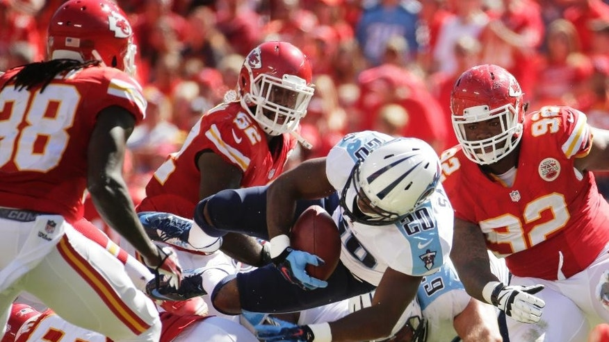 Tennessee Titans running back Bishop Sankey (20) flies through the air between Kansas City Chiefs defenders Ron Parker, left, James-Michael Johnson (52) and Dontari Poe (92) in the second half of an NFL football game in Kansas City, Mo., Sunday, Sept. 7, 2014. (AP Photo/Charlie Riedel)