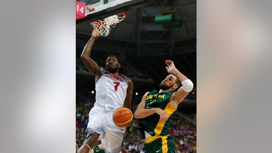 United States's Kenneth Faried, left, dunks the ball in front of Lithuania's Jonas Valanciunas during their Basketball World Cup semifinal match at the Palau Sant Jordi in Barcelona, Spain, Thursday, Sept. 11, 2014. (AP Photo/Emilio Morenatti)