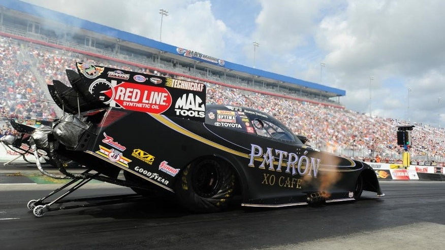 In this photo provided by the NHRA, Alexis DeJoria races to the No. 1 qualifying position in Funny Car at the Pep Boys NHRA Carolina Nationals drag races at zMAX Dragway on Saturday, Sept. 13, 2014, in Concord, N.C. She opens eliminations against Dave Richards. (AP Photo/NHRA, Marc Gewertz)