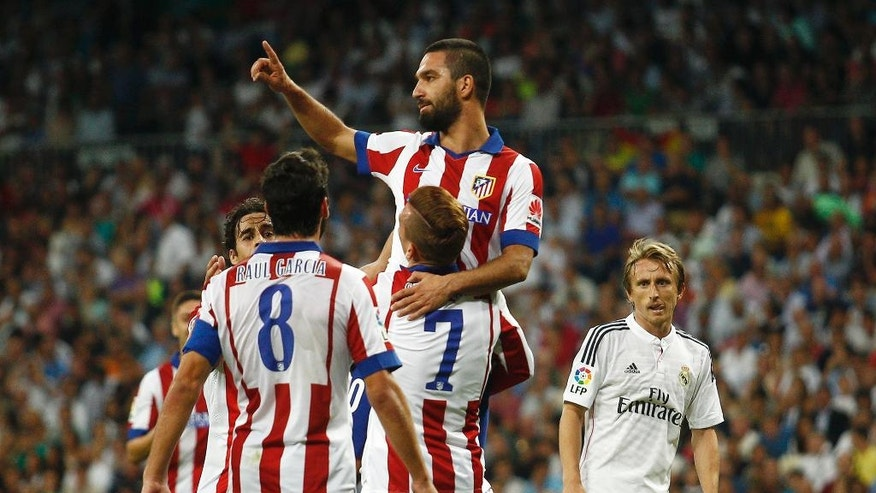 Atletico de Madrid's Arda Turan, top, celebrates his a goal with teammates during a Spanish La Liga soccer match against Real Madrid at the Santiago Bernabeu stadium in Madrid, Spain, Saturday, Sept. 13, 2014. (AP Photo/Gabriel Pecot)