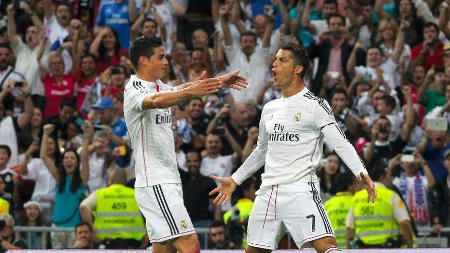 Real Madrid's Cristiano Ronaldo, right, celebrates his goal with teammate James Rodriguez during a Spanish La Liga soccer match against Atletico de Madrid  at the Santiago Bernabeu stadium in Madrid, Spain, Saturday, Sept. 13, 2014. (AP Photo/Gabriel Pecot)