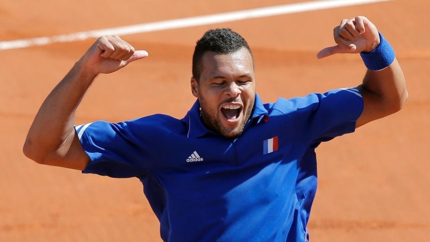 France's Jo-Wilfried Tsonga celebrates after defeating Lukas Rosol of the Czech Republic during their single match in the semifinal of the Davis Cup at the Roland Garros stadium, in Paris, Friday, Sept. 12, 2014. (AP Photo/Christophe Ena)