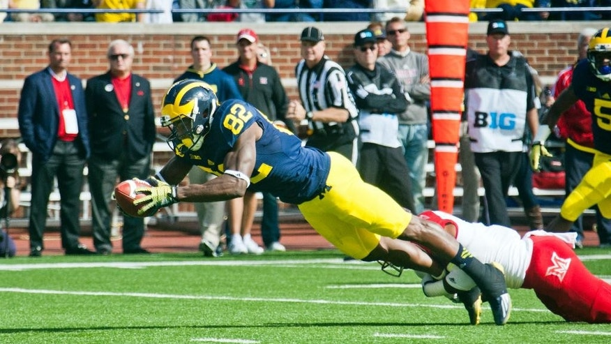 Michigan wide receiver Amara Darboh (82) dives for a touchdown, defended by Miami (Ohio) defensive back Quinten Rollins (2) in the first quarter of an NCAA college football game in Ann Arbor, Mich., Saturday, Sept. 13, 2014. (AP Photo/Tony Ding)