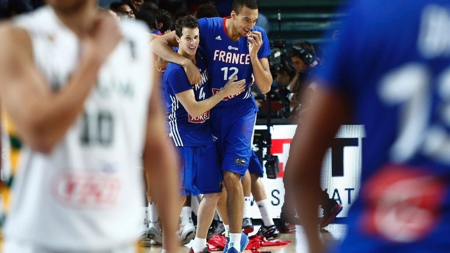 France's Rudy Gobert and Thomas Heurtel celebrate their bronze medal at the end of the match during the 3rd place final of the World Basketball between France and Lithuania at the Palacio de los Deportes stadium in Madrid, Spain, Saturday, Sept. 13, 2014. (AP Photo/Andres Kudacki)