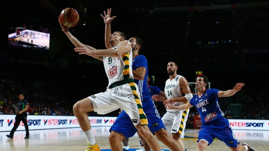 Lithuania's Renaldas Seibutis pushes the ball up the basket against France's Joffrey Lauvergne during the 3rd place final of the World Basketball between France and Lithuania at the Palacio de los Deportes stadium in Madrid, Spain, Saturday, Sept. 13, 2014. (AP Photo/Andres Kudacki)