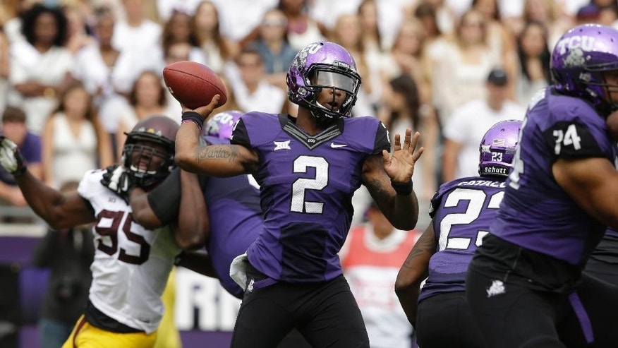 TCU quarterback Trevone Boykin (2) passes the ball as Minnesota defensive lineman Hendrick Ekpe (95) is blocked  during the first half of an NCAA college football game, Saturday, Sept. 13, 2014, in Fort Worth, Texas. (AP Photo/LM Otero)