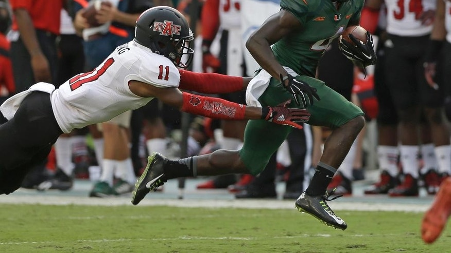 Arkansas State defensive back Sterling Young (11) tries to stop Miami wide receiver Phillip Dorsett (4) in the first half of an NCAA college football game in Miami Gardens, Fla., Saturday, Sept. 13, 2014. (AP Photo/Alan Diaz)