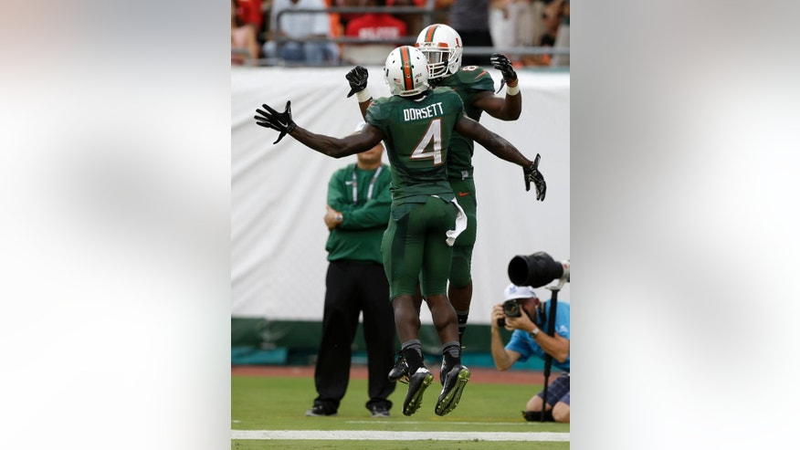 Miami wide receiver Phillip Dorsett (4) celebrates with Duke Johnson, background,  after Johnson scored a touchdown against Arkansas State in the first half of an NCAA college  football game in Miami Gardens, Fla., Saturday, Sept. 13, 2014. (AP Photo/Alan Diaz)