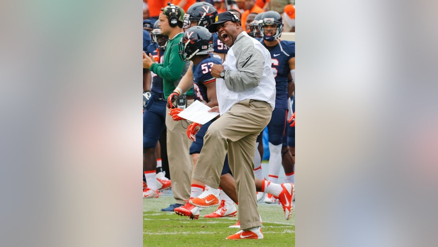 Virginia head coach Mike London cheers on his team during the first half of an NCAA college football game against Louisville in Charlottesville, Va., Saturday, Sept. 13, 2014. (AP Photo/Steve Helber)
