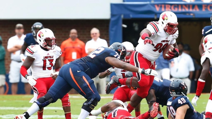 Louisville defensive end Sheldon Rankins (98) gains extra yardage after a fumble recovery as Virginia offensive tackle Eric Smith (72) makes the stop during the first half of an NCAA college football game in Charlottesville, Va., Saturday, Sept. 13, 2014. (AP Photo/Steve Helber)