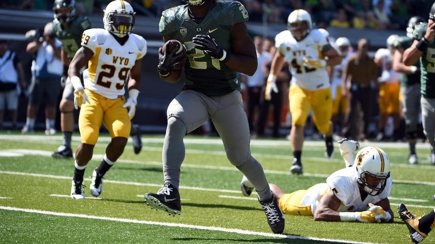 Oregon running back Royce Freeman (21) scores a touchdown during the third quarter of an NCAA college football game against Wyoming at Autzen Stadium, Saturday, Sept. 13, 2014, in Eugene, Ore. (AP Photo/Steve Dykes)