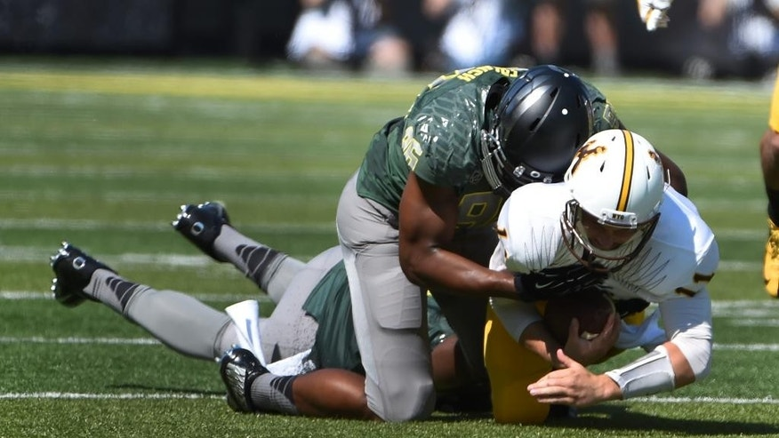 Oregon linebacker Christian French (96) sacks Wyoming quarterback Colby Kirkegaard (11 during the second quarter of an NCAA college football game at Autzen Stadium, Saturday, Sept. 13, 2014, in Eugene, Ore. (AP Photo/Steve Dykes)