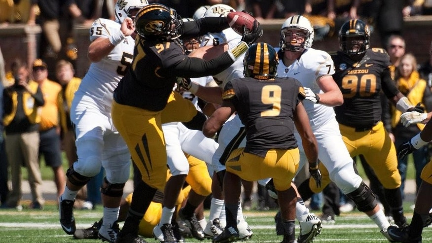Missouri's Josh Augusta, center, pulls down an interception in a crowd of players during the third quarter of an NCAA college football game against Central Florida, Saturday, Sept. 13, 2014, in Columbia, Mo. (AP Photo/L.G. Patterson)