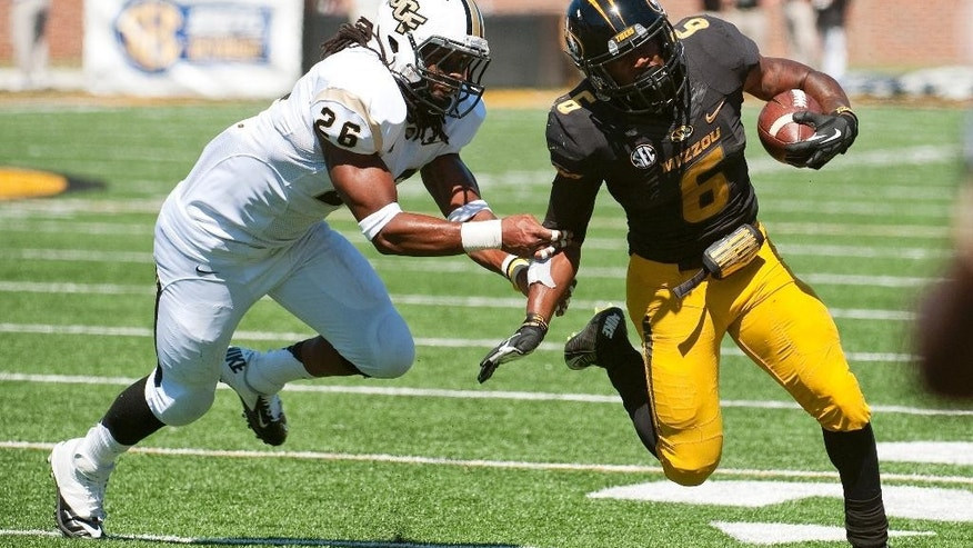 Missouri running back Marcus Murphy, right, runs around Central Florida's Clayton Geathers, left, during the fourth quarter of an NCAA college football game Saturday, Sept. 13, 2014, in Columbia, Mo. Missouri won the game 38-10. (AP Photo/L.G. Patterson)