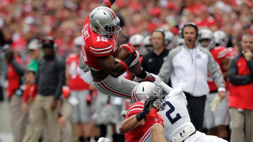 Ohio State running back Ezekiel Elliott, top, tries to jump over Kent State defenders during the first quarter of an NCAA college football game Saturday, Sept. 13, 2014, in Columbus, Ohio. (AP Photo/Jay LaPrete)