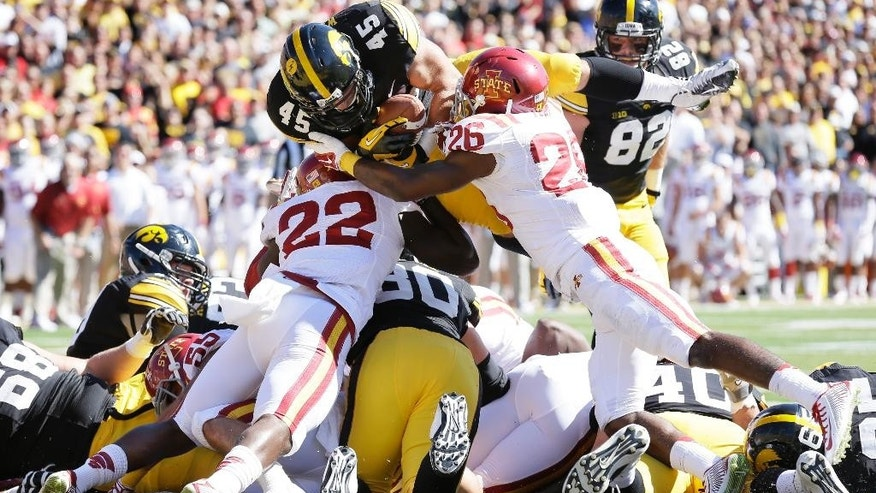 Iowa running back Mark Weisman (45) scores on a 1-yard touchdown run over Iowa State defensive back T.J. Mutcherson (22) and defensive back Qujuan Floyd (26) during the first half of an NCAA college football game, Saturday, Sept. 13, 2014, in Iowa City, Iowa. (AP Photo/Charlie Neibergall)