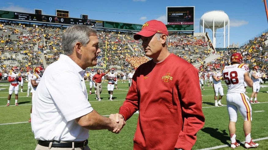 Iowa head coach Kirk Ferentz, left, greets Iowa State coach Paul Rhoads before an NCAA college football game, Saturday, Sept. 13, 2014, in Iowa City, Iowa. (AP Photo/Charlie Neibergall)