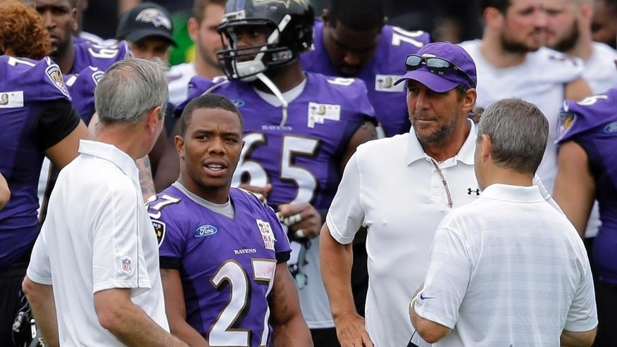 FILE - In this July 24, 2014, file photo, Baltimore Ravens running back Ray Rice, second from left, speaks with team president Dick Cass, left, owner Steve Bisciotti, second from right, and Kevin Byrne, senior vice president for public and community relations, after a training camp practice in Owings Mills, Md. The Ravens have cut Ray Rice. Hours after the release of a video that appears to show Rice striking his then-fiancee in February, the team terminated his contract Monday, Sept. 8, 2014.(AP Photo/File)