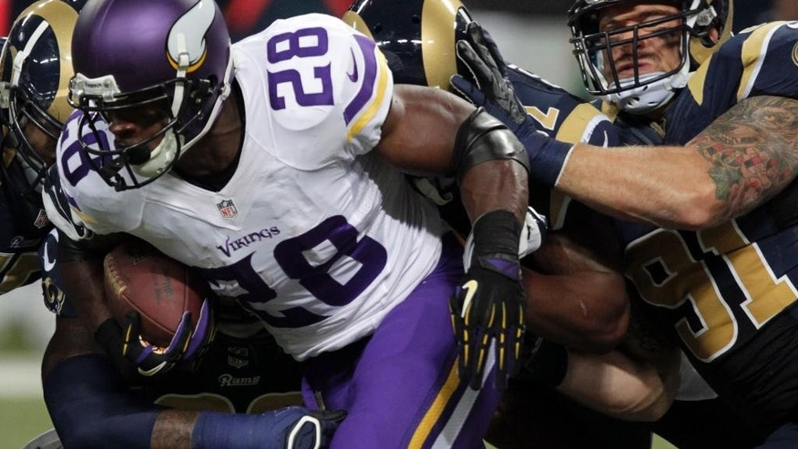 Minnesota Vikings running back Adrian Peterson, right, gets a block from offensive tackle Matt Kalil as St. Louis Rams defensive end Robert Quinn, left, gives chase during the third quarter an NFL football game Sunday, Sept. 7, 2014, in St. Louis. (AP Photo/L.G. Patterson)