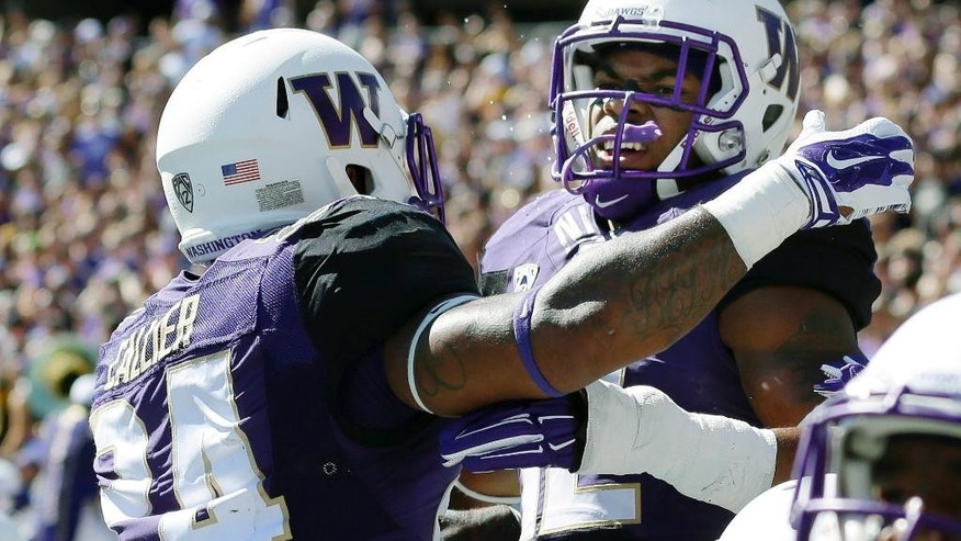 Washington running back Jesse Callierin (24) hugs running back Dwayne Washington, right, after Washington scored a touchdown the first half of an NCAA college football game Saturday, Sept. 13, 2014, in Seattle. (AP Photo/Ted S. Warren)