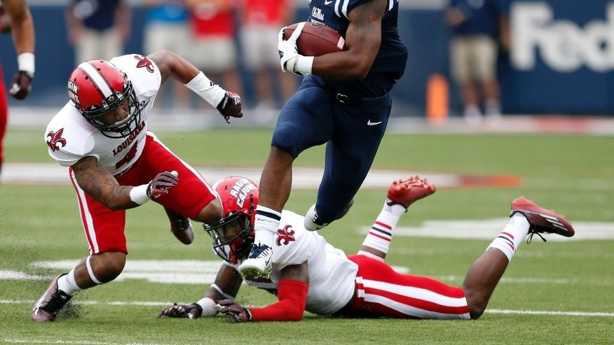 Mississippi running back I'Tavius Mathers (5) hurdles over Louisiana-Lafayette defenders on his way to a 56-yard touchdown run during the first quarter at an NCAA college football game at Vaught-Hemingway Stadium in Oxford, Miss., Saturday, Sept. 13, 2014. (AP Photo/Rogelio V. Solis)