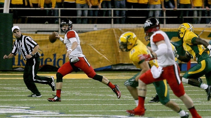Incarnate Word quarterback Taylor Woods is pursued by North Dakota State defenders as he a rolls out to pass in the first half of an NCAA college football game Saturday, Sept. 13, 2014, at Fargodome in Fargo, N.D. (AP Photo/Bruce Crummy)