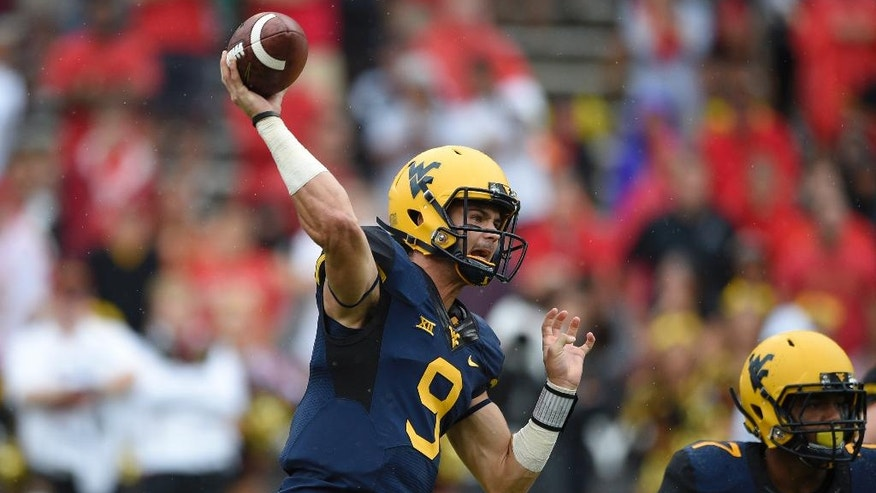 West Virginia quarterback Clint Trickett (9) passes against Maryland during the first half of an NCAA football game, Saturday, Sept. 13, 2014, in College Park, Md. (AP Photo/Nick Wass)