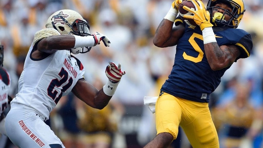 West Virginia wide receiver Mario Alford (5) catches a pass against Maryland defensive back Sean Davis (21) during the first half of an NCAA football game, Saturday, Sept. 13, 2014, in College Park, Md. Alford scored a touchdown on the play. (AP Photo/Nick Wass)