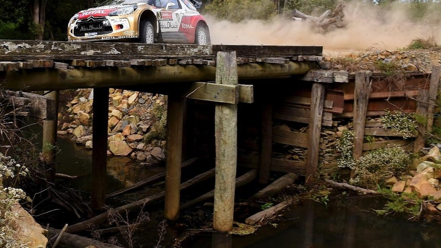 In this photo provided by Rally Australia,  Kris Meeke of Britain and and co-driver Paul Nagle of Ireland, race their car during the Australian leg of the World Rally Championship near Coffs Harbour, Saturday, Sept. 13, 2014. (AP Photo/Rally Australia) EDITORIAL USE ONLY