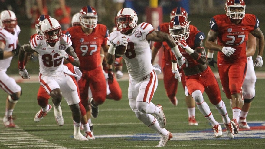 Nebraska's Ameer Abdullah runs through the Fresno State defense on the way to a touchdown in the first half of an NCAA college football game in Fresno, Calif., Saturday, Sept. 13, 2014. (AP Photo/Gary Kazanjian)