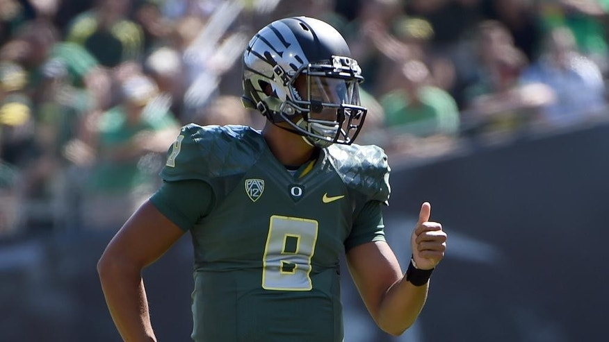 Oregon quarterback Marcus Mariota (8) signals to his teammates during the second quarter of an NCAA college football game against Wyoming at Autzen Stadium on Saturday, Sept. 13, 2014, in Eugene, Ore. (AP Photo/Steve Dykes)