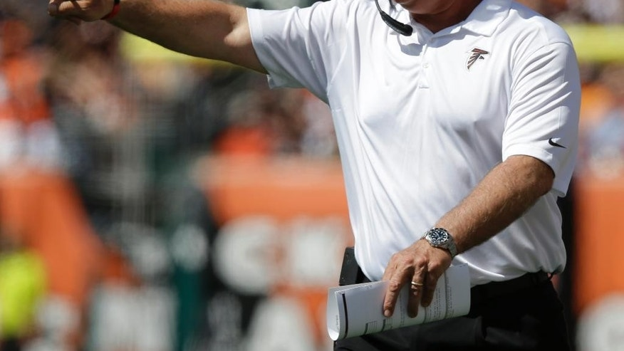 Atlanta Falcons head coach Mike Smith yells on the sidelines in the first half of an NFL football game against the Cincinnati Bengals, Sunday, Sept. 14, 2014, in Cincinnati. (AP Photo/Michael Conroy)