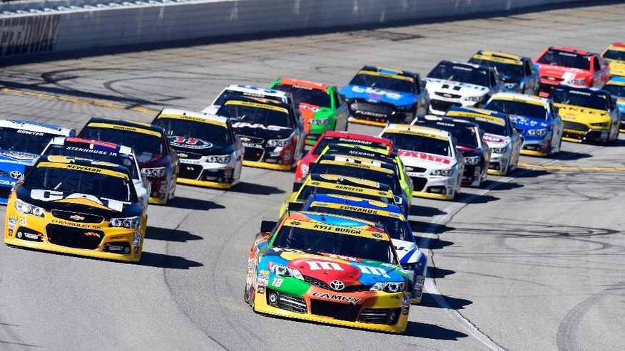 Kyle Busch (18) leads the field at the start of the NASCAR Sprint Cup series auto race at Chicagoland Speedway in Joliet, Ill., Sunday, Sept. 14, 2014. (AP Photo/Paul J. Bergstrom)