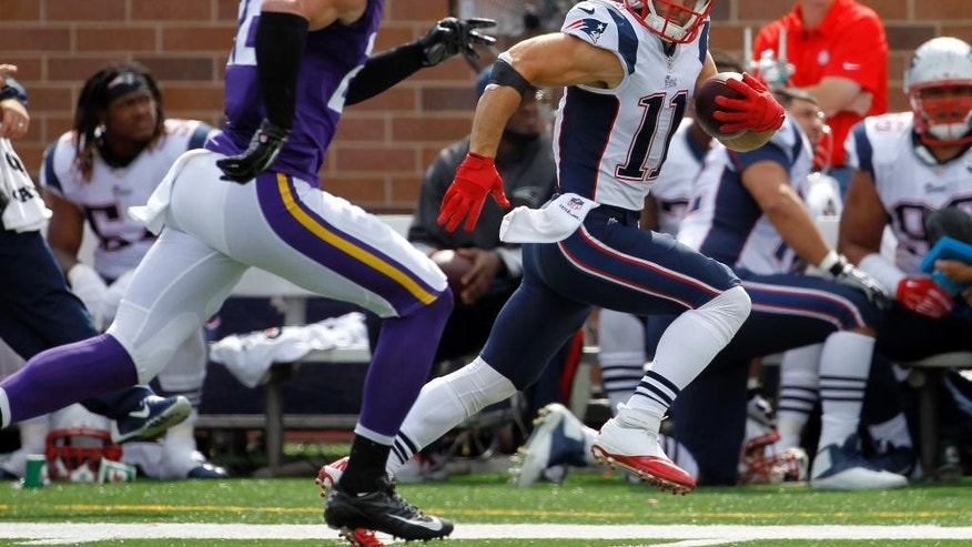 New England Patriots wide receiver Julian Edelman, right, runs with the ball past Minnesota Vikings free safety Harrison Smith after catching a pass during the second quarter of an NFL football game Sunday, Sept. 14, 2014, in Minneapolis. Edelman picked up 44 yards on the play. (AP Photo/Ann Heisenfelt)