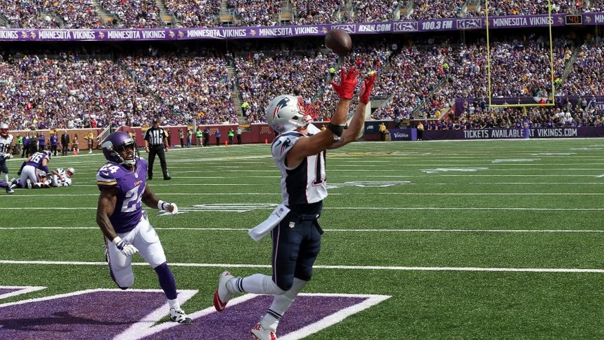 New England Patriots wide receiver Julian Edelman, right, catches a 9-yard touchdown pass as Minnesota Vikings cornerback Captain Munnerlyn watches during the second quarter of an NFL football game Sunday, Sept. 14, 2014, in Minneapolis. (AP Photo/Jim Mone)