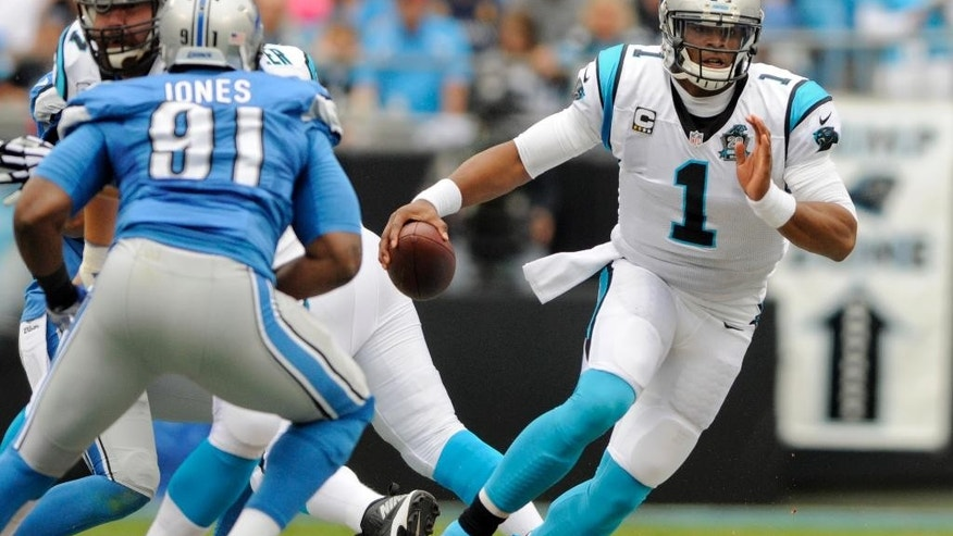 Carolina Panthers quarterback Cam Newton (1) scrambles as Detroit Lions defensive end Jason Jones (91) pursues during the first half of an NFL football game in Charlotte, N.C., Sunday, Sept. 14, 2014. (AP Photo/Mike McCarn)
