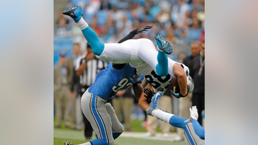 Carolina Panthers' Greg Olsen (88) is upended by Detroit Lions' Devin Taylor (92) after a catch during the first half of an NFL football game in Charlotte, N.C., Sunday, Sept. 14, 2014. (AP Photo/Mike McCarn)