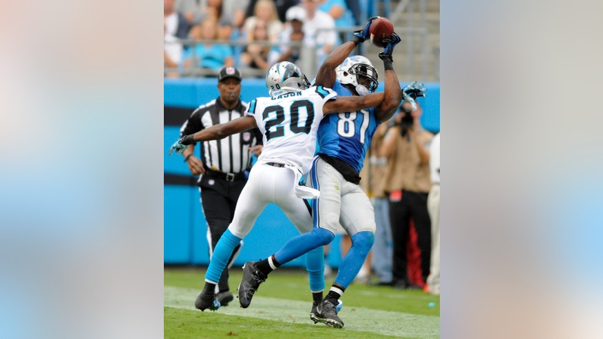 Detroit Lions' Calvin Johnson (81) catches a pass over Carolina Panthers' Antoine Cason (20) during the first half of an NFL football game in Charlotte, N.C., Sunday, Sept. 14, 2014. (AP Photo/Mike McCarn)